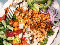 """An overhead shot of a composed salad in bright, outdoor light. Salad is photographed on a link plate and includes: halved cherry tomatoes, kale, sliced cucumber, sliced avocado, chickpeas, toasted almond """"bacon"""", sliced red onion, and bits of crumbled vegan cheese."""