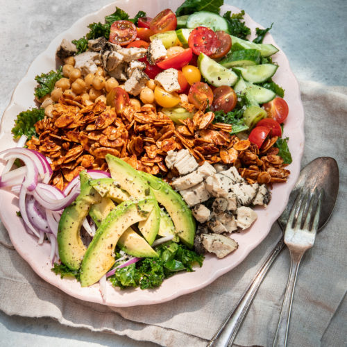 """A 3/4 angle shot of a composed salad in bright, outdoor light. Salad is photographed on a link plate and includes: halved cherry tomatoes, kale, sliced cucumber, sliced avocado, chickpeas, toasted almond """"bacon"""", sliced red onion, and bits of crumbled vegan cheese."""