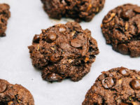 A 3/4 angle shot of chocolate zucchini muffin tops on a white parchment background.