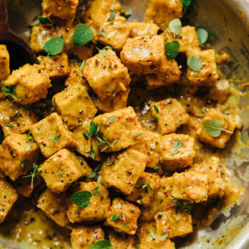 An up close, overhead shot of saucy chunks of tempeh in a skillet. The sauce is golden yellow and the tempeh is garnished with fresh thyme and oregano leaves.
