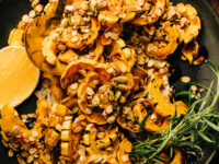 An overhead shot of roasted delicata squash pieces topped with rosemary granola and spiced maple syrup; all on top of a matte black plate with a wedge of lemon to the side.