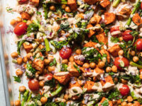 An up close, overhead shot of roasted sweet potatoes, broccoli rabe, chickpeas, and cherry tomatoes drizzled with a creamy peanut sauce. There are garnishes of diced red onion and pumpkin seeds on top as well. All components are contained in a sheet pan.