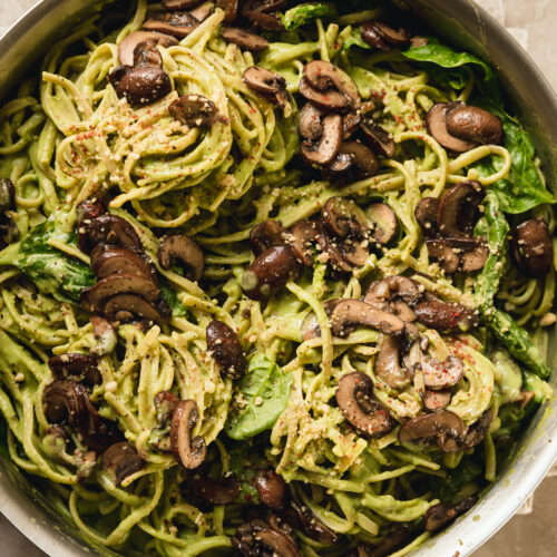 pinach and mushroom pasta in a stainless steel skillet. The pasta is creamy and pale green and topped with brown, sautéed mushrooms.