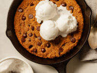 An up overhead shot of a slightly orange pumpkin chocolate chip skillet cookie topped with 3 scoops of vanilla ice cream.